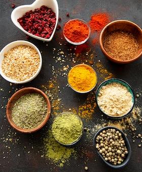 Erbe aromatiche e spezie colorate e aromatiche su uno sfondo scuro
