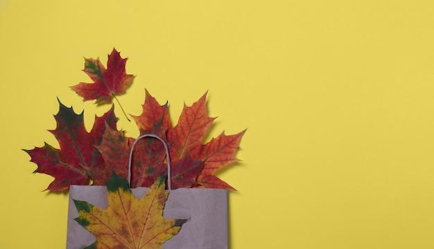 Foglie autunnali colorate in un sacchetto di carta artigianale su sfondo giallo. sconti autunnali e concetto di shopping