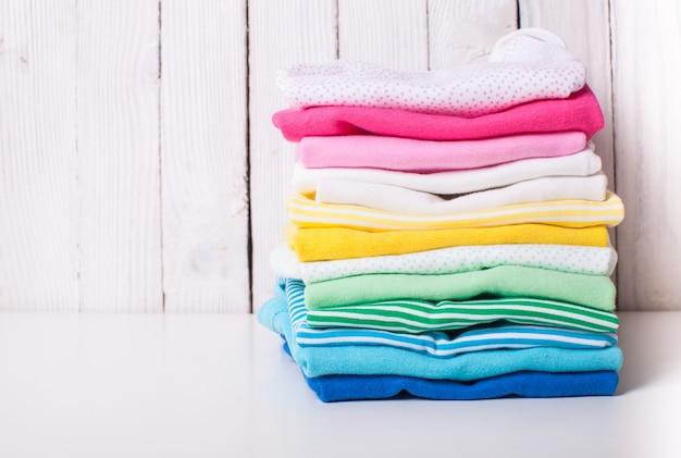 Vestiti colorati per bambini di pile piegate su sfondo bianco