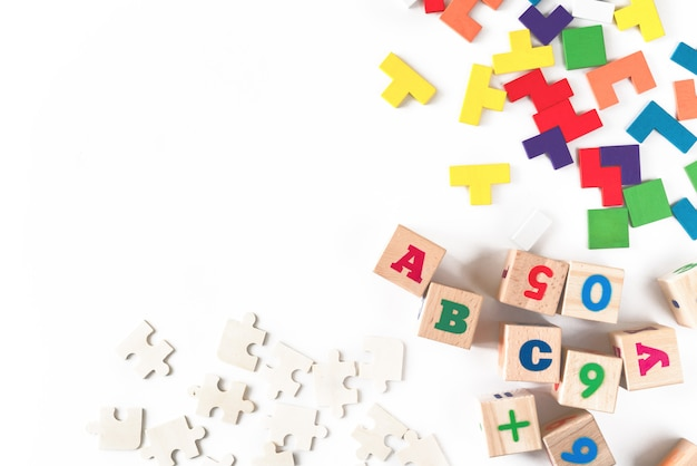 Giocattoli variopinti dei bambini del bambino su fondo bianco. telaio dallo sviluppo di blocchi colorati, automobili e aerei, puzzle. vista dall'alto. disteso. copia spazio per il testo