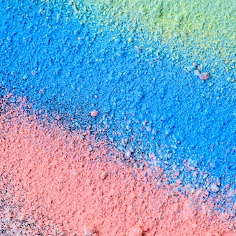 Sfondo colorato di gesso in polvere. particelle di polvere multicolore schizzate su sfondo nero.