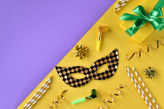 Sfondo colorato di maschera, regalo e stelle filanti. layout piatto