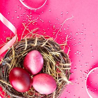Sfondo colorato con uova di pasqua su sfondo rosso. felice pasqua concetto. può essere utilizzato come poster, sfondo, biglietto di auguri. appartamento laico, vista dall'alto, copia dello spazio. foto di studio
