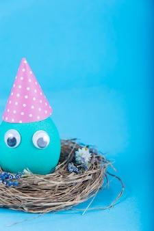 Sfondo colorato con uovo carino divertente di pasqua su sfondo blu.