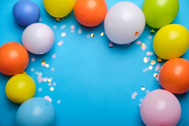 Palloncini colorati e coriandoli sulla vista del piano d'appoggio blu.