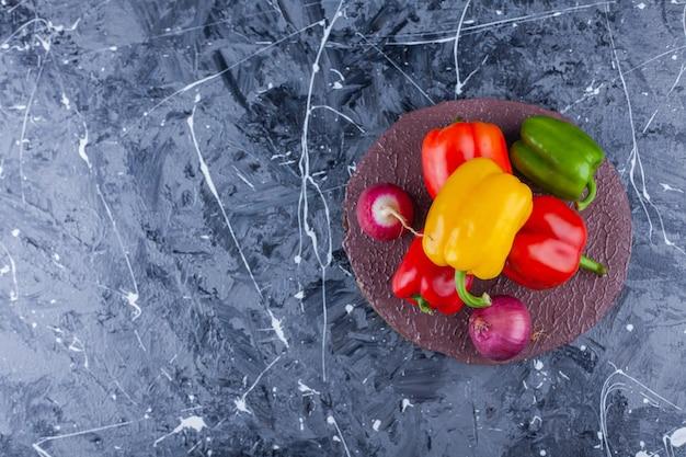 Peperoni dolci colorati, cipolla e ravanello rosso sul pezzo di legno.