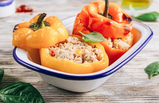 Peperoni di paprica ripieni di campana colorati con carne, riso e verdure su fondo di legno bianco. messa a fuoco selettiva