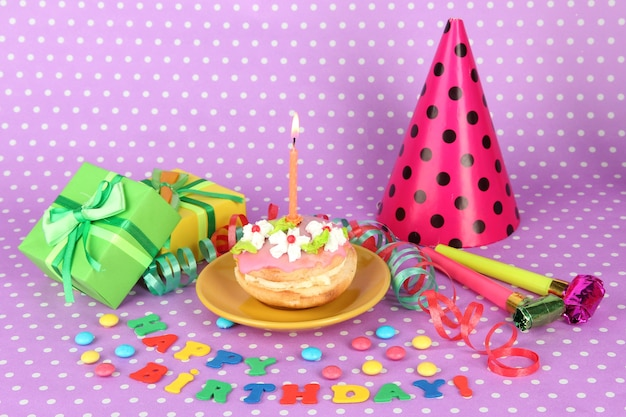 Torta di compleanno colorata con candela e regali sullo spazio rosa