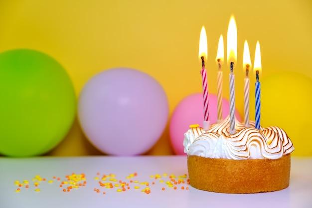 Una torta di compleanno colorata con candele e coriandoli su sfondo giallo