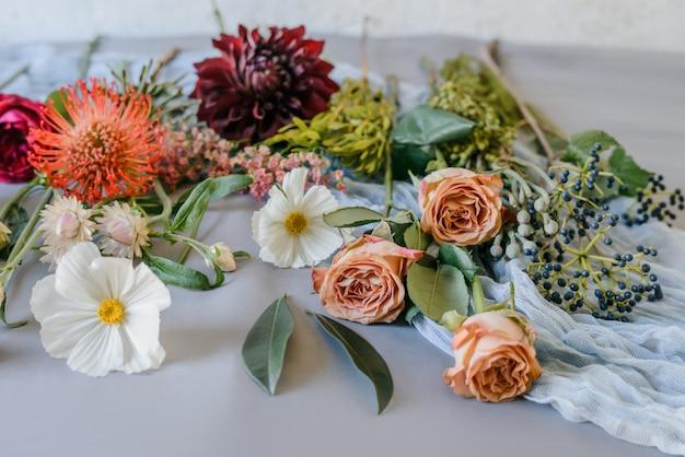 Mazzo variopinto dei fiori del giardino estivo. fiordalisi sul vecchio tavolo malandato. sfondo floreale vintage.