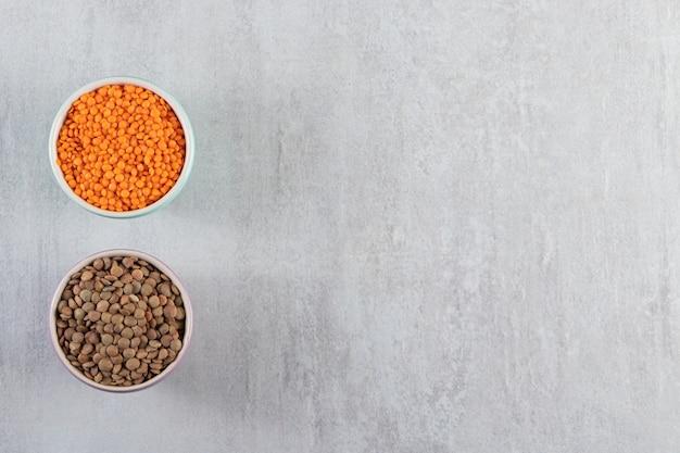 Ciotole colorate con lenticchie crude e grano saraceno su sfondo di pietra.