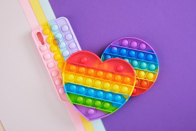 Custodia colorata e luminosa per uno smartphone sotto forma di un giocattolo antistress alla moda e alla moda pop it e due giocattoli pop it, sfondo geometrico multicolore