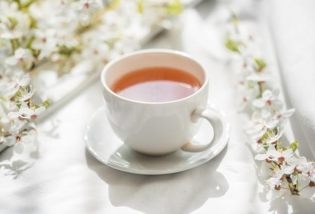 Motivo floreale luminoso colorato con tazza da tè. disposizione piatta.