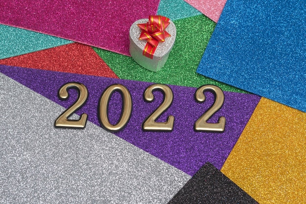 Su uno sfondo colorato e brillante di capodanno, una confezione regalo d'argento con un fiocco rosso e numeri dorati 2022. concetto per la carta di capodanno, invito.