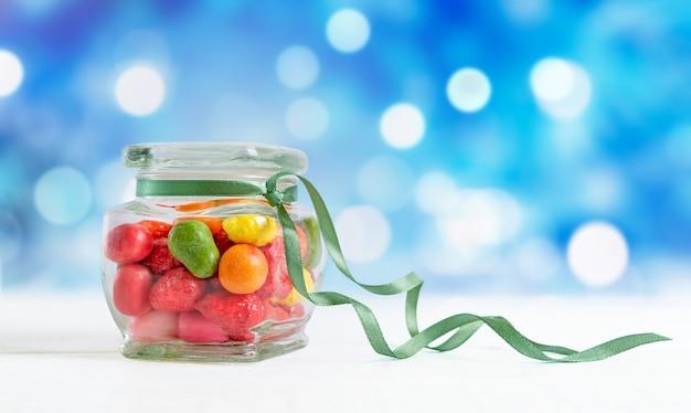 Caramelle colorate in un barattolo su uno sfondo blu bokeh. i dolci delle feste.