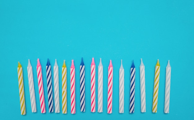 Candele colorate sono disposte in fila per una torta di compleanno su sfondo blu