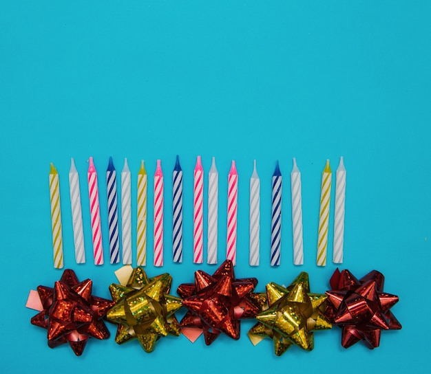 Candele colorate per una torta di compleanno e fiocchi per il confezionamento su sfondo blu