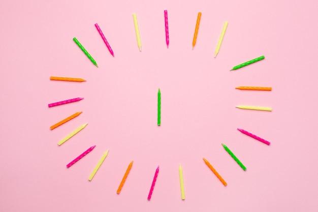 Candele colorate per cornice torta di compleanno su sfondo rosa
