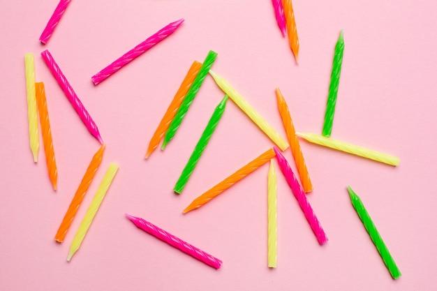 Candele colorate per torta di compleanno su uno sfondo rosa