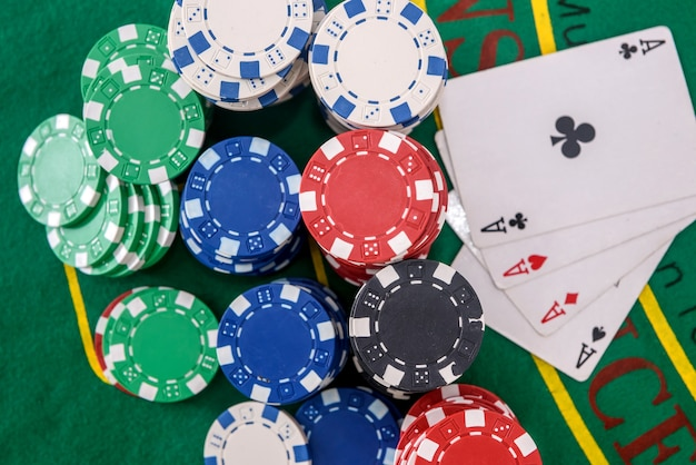 Fiches del casinò colorate sul tavolo da poker verde da vicino