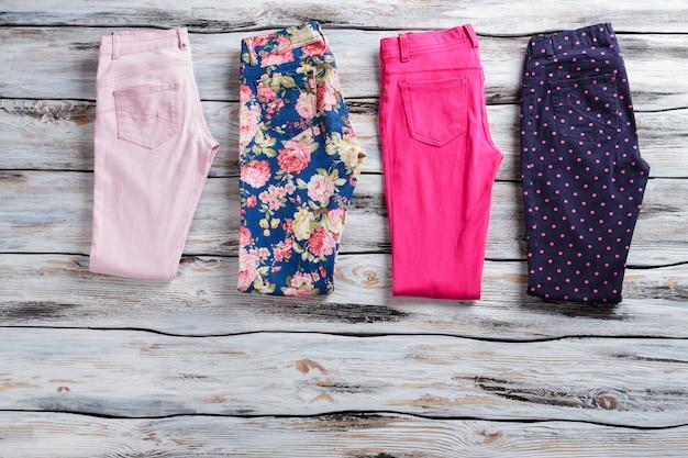 Pantaloni casual colorati. pantaloni piegati di colore brillante. nuovissimi pantaloni estivi da bambina. vetrina in legno con oggetti popolari.