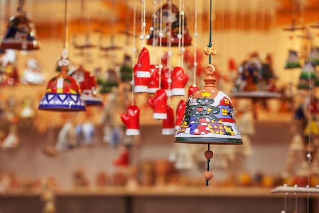 Campane in ceramica colorate vendute sul mercatino di natale in europa. regalo di souvenir in argilla campana in fiera.