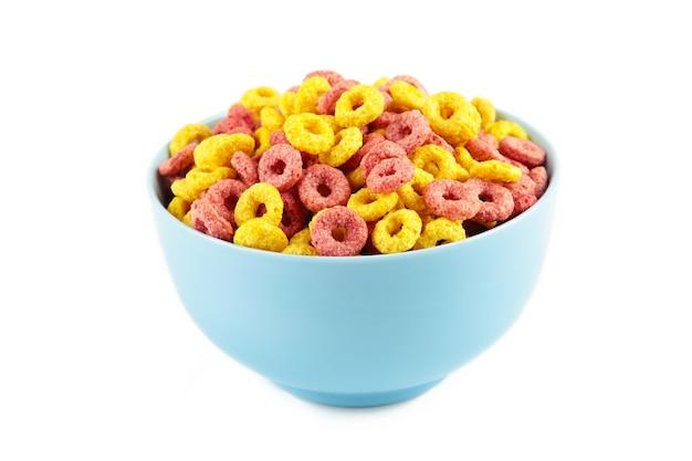 Anelli di anello di cereali colorati sulla ciotola blu isolato su sfondo bianco. cibo per la colazione.