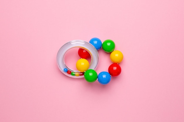 Sonaglio colorato per bambini su uno sfondo rosa, giocattolo per bambini piccoli e neonati vista dall'alto
