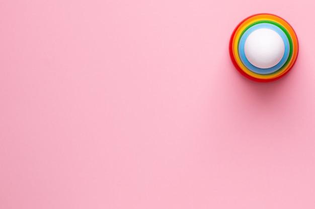 Piramide di legno per bambini colorati su sfondo rosa, giocattolo per bambini e neonati con vista adove copyspace