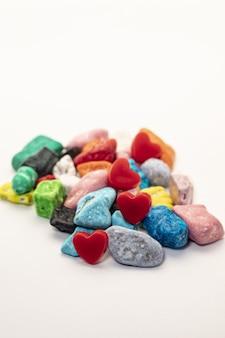 Pietre variopinte della caramella di cioccolato su priorità bassa bianca.