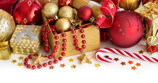 Colorate decorazioni natalizie - palline, ghirlande e confezione regalo da vicino isolato su bianco