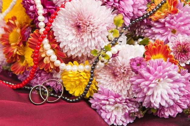 Crisantemi colorati e fiori di margherita su un tessuto bordeaux con fedi nuziali e perline