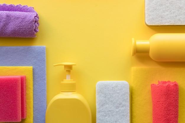 Set di pulizia colorato per diverse superfici in cucina, bagno e altre stanze. posto vuoto per testo o logo su sfondo giallo. concetto di servizio di pulizia. articoli di pulizia pulizia regolare.