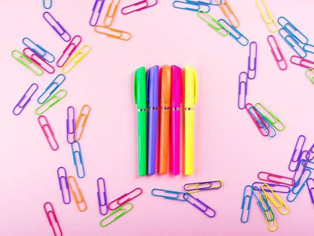 Struttura variopinta del modello delle penne e della clip sul rosa