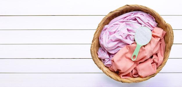 Vestiti colorati con misurino di detersivo in polvere nel cesto della biancheria su fondo di legno bianco. copia spazio