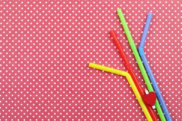 I tubi da cocktail colorati giacciono su uno sfondo di colore brillante