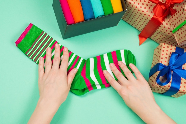 Collezione colorata di calze di cotone come regalo nelle mani di una donna. regalo.