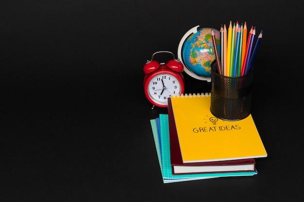 Colorata collezione di materiale scolastico impostato su sfondo nero. di nuovo a scuola. grandi idee