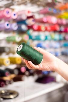 Coni colorati e rocchetti di filo in un atelier sartoria, industria dell'abbigliamento, concetto di laboratorio di design.