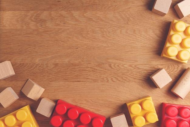 Blocchetti e cubi di costruzione variopinti su fondo di legno come pensionante della struttura dei giocattoli. disteso. vista dall'alto