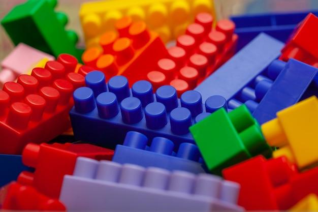 Un colorato set costruttore, che si trova sul pavimento di una casa, primo piano. giochi educativi per bambini. cubi di design per bambini in plastica, messa a fuoco selettiva.