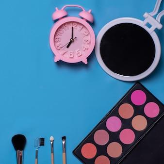 Pennelli cosmetici colorati, ombretti, specchio, sveglia su sfondo blu. insieme di trucco. lay piatto, copia spazio, sfondo per il design. tempo per il trucco