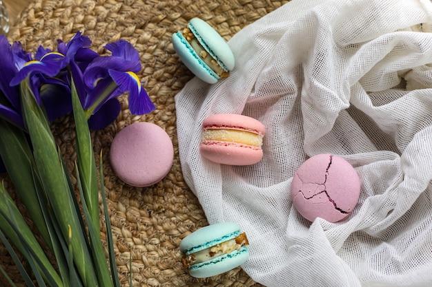 Macarons francesi tradizionali casalinghi deliziosi variopinti - dessert francese elegante aromi naturali di frutta e bacche, ripieno cremoso e fiori di iris blu su stoffa per la festa della mamma di san valentino.