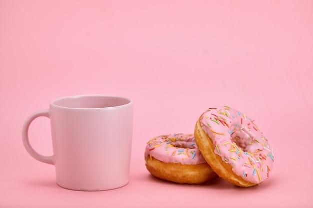 Composizione colazione ciambelle colorate con stili di colore rosa. gioco di colori, rosa su rosa. dolce vita, colazione alla vaniglia.