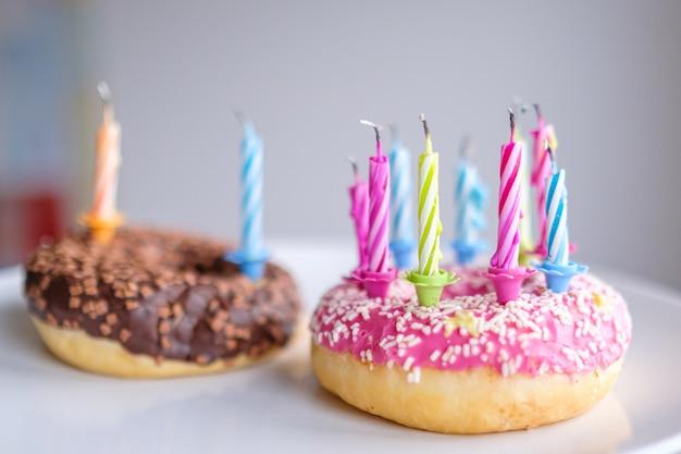 Ciambelle colorate con glassa rosa e cioccolato con candeline per festa di compleanno