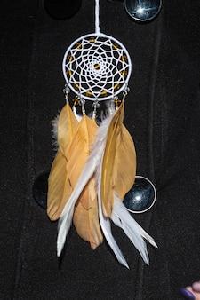 Acchiappasogni colorato fatto di piume, perline e corde in pelle, appeso, fatto a mano