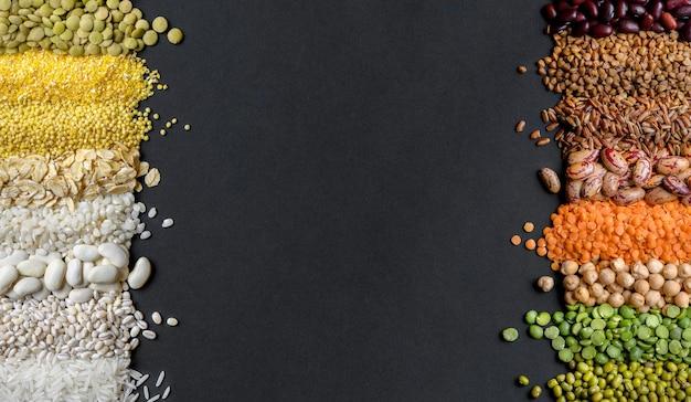 Cereali e legumi secchi colorati: lenticchie, piselli di riso, fagioli, miglio, ceci su sfondo nero. vista dall'alto. copia spazio
