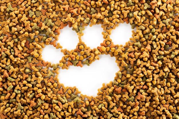 Cibo per cani essiccato colorato e stampa della zampa di cane o gatto. sfondo di banner di alimentazione animale del grano con lo spazio della copia per il disegno del testo.