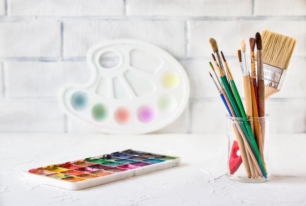 Insieme variopinto della compressa dell'acquerello asciutto e tavolozza di plastica bianca e pennelli e matite su bianco