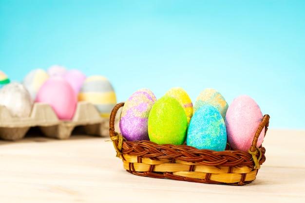 Uova di pasqua colorate nel carrello sul tavolo sulla superficie blu
